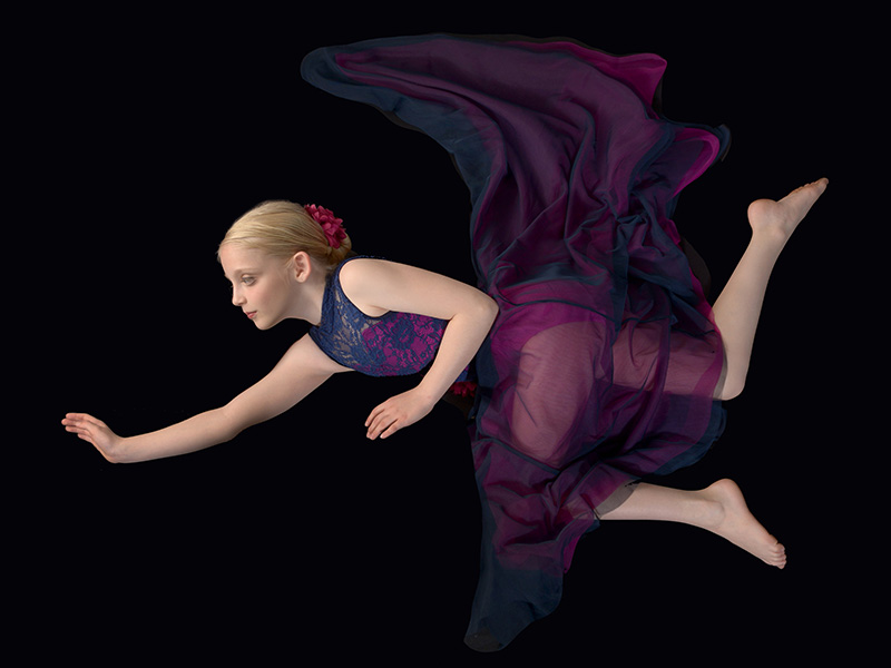 dayton dance conservatory dancer surreal flying pose in colorful outfit